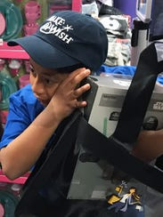 José Garcia hugs his Star Wars light saber box from The Disney Store, one of his first purchases on his Make A Wish shopping spree.