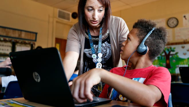 Shondra Collins, a fifth grade teacher at York Elementary, helps Dana Harris, 10, with a question as the class works on a project on their laptop computers at the Springfield, Mo. school on Oct. 22, 2015.