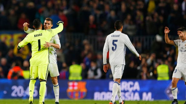 Real Madrid's Cristiano Ronaldo, second left, celebrates with goalkeeper Keylor Navas, left, at the end of the Spanish La Liga soccer match between FC Barcelona and Real Madrid at the Camp Nou stadium in Barcelona, Spain, Saturday, Dec. 3, 2016. The match ended in a 1-1 draw. (AP Photo/Francisco Seco)