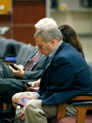 """Paul """"P.J."""" Tucci checks his phone outside of the courtroom"""