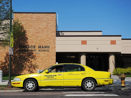 A Yellow Cab taxi sits outside Horace Mann Elementary
