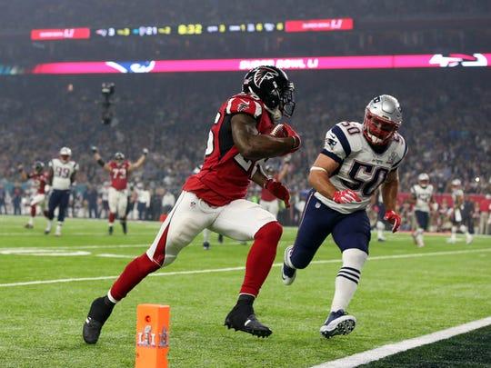 Atlanta Falcons running back Tevin Coleman scores a touchdown against New England Patriots linebacker Rob Ninkovich during the third quarter during Super Bowl LI at NRG Stadium.
