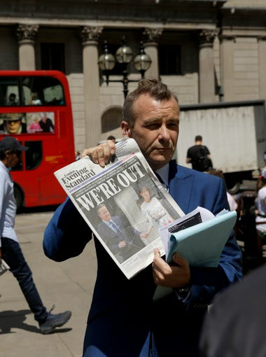 A journalist holds up a copy of the London Evening Standard newspaper as he takes part in a television broadcast outside the Bank of England in the City of London, on June 24, 2016