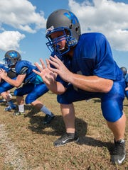 Woodbridge High School football linemen Brian Ireland runs linemen drills at practice.