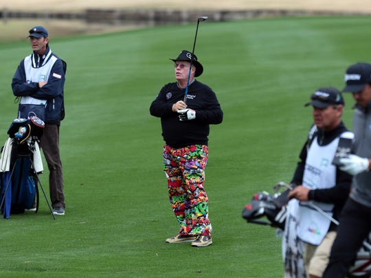 Amateur golfer Dave Colby hits his approach during