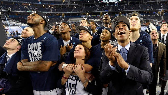 "Connecticut Huskies head coach Kevin Ollie watches ""one shining moment"" on the scoreboard with his players after defeating the Kentucky Wildcats in the championship game of the Final Four."