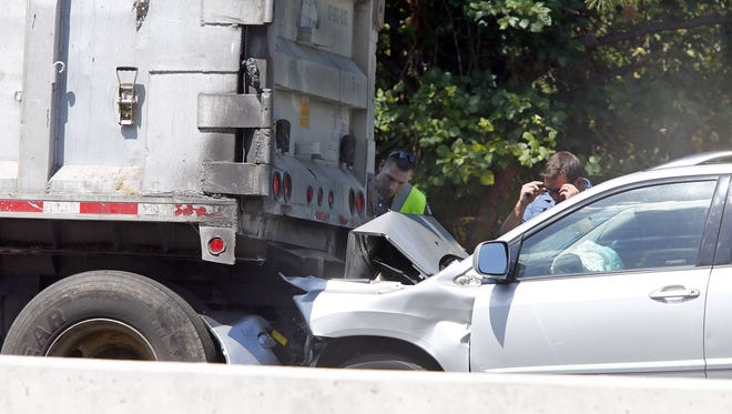 Police officers look over the car the struck a stopped tractor trailer on Route 70 westbound at Riverview Drive in Wall Township, Friday, August 12, 2016.  The accident forced the closure of Rt 70 at Route 34 caused extensive traffic in the area.