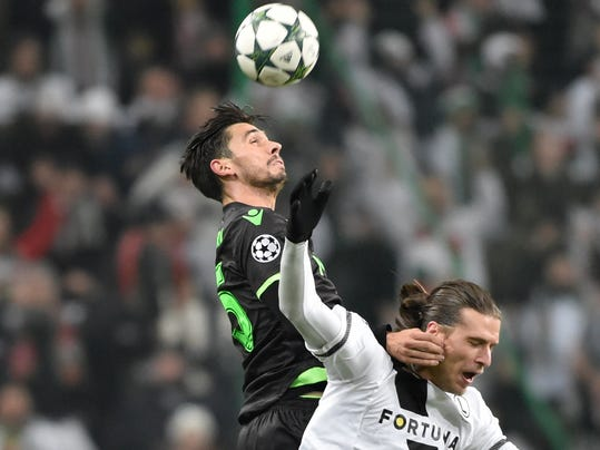 Legia's Aleksandar Prijovic, below, jumps the ball with Sporting Lisbon's Paulo Oliveira during the Champions League group stage soccer match between Legia Warsaw and Sporting Lisbon, at Stadion Wojska Polskiego, in Warsaw, Poland, Wednesday, Dec. 7, 2016. (AP Photo/Alik Keplicz)