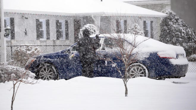 A motorist clears snow from her car at Valley Avenue and Linda Lane in Vineland on Thursday, March 5, 2015.  Staff photo/Charles J. Olson