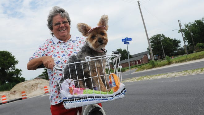 Linda Mears and her dog Precious go for a bike ride on Bay Avenue in Cape Charles, Va. on Tuesday, June 21, 2016.