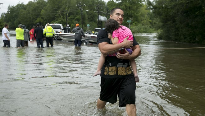 Nathan Welch carries his daughter, Elisa, 3, out of the flood on Tram Road after being rescued by boat from his home in Beaumont, Texas, after Tropical Storm Harvey on Wednesday Aug. 30, 2017.