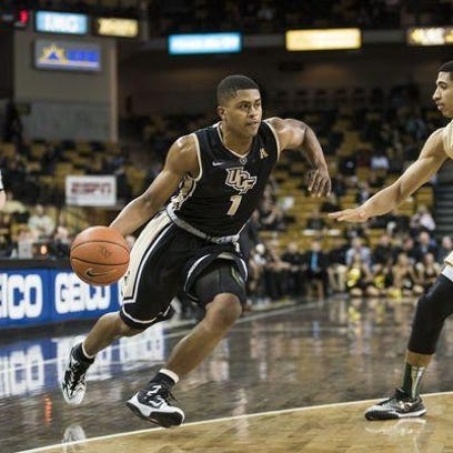 UCF's B.J. Taylor dribbles past a USF defender during