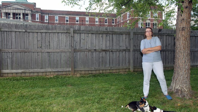Holly Hamilton in the backyard of her home on Belkenton Avenue, Silverton, with her Basenjis dogs, Lotus and Beck. She opposes a plan to turn the former St. Theresa Home next to her home into a psychiatric care facility. She purchased her home nine years ago in part because it has a 300-foot deep backyard for her dogs. She is also concerned about traffic on what is now a dead end street and the fact that the parking lot overlooks her backyard.