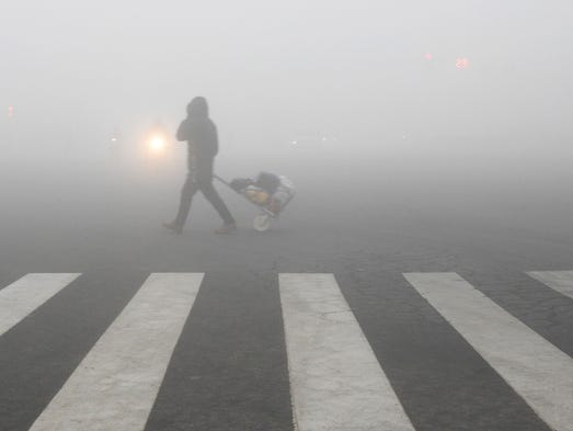 A pedestrian crosses a smog-shrouded street in Lianyungang,