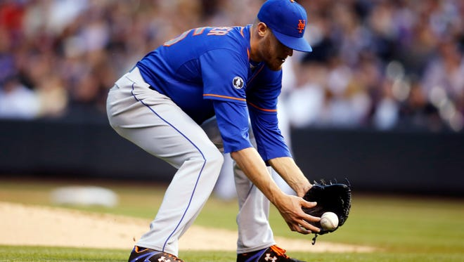 Mets starting pitcher Zack Wheeler fails to hold on to a ground ball hit by Colorado Rockies pitcher Jorge De La Rosa in the second inning at Coors Field in Denver on Friday night.
