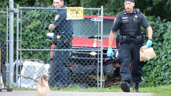 A sheriff's deputy with the Plymouth County Bureau of Criminal Investigation collects evidence at the scene of a stabbing at 78 Linwood St. in Brockton, Thursday, July 16, 2020.