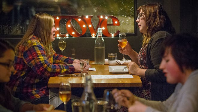 "Megan Robertson and fiance Katie Blair chat during a dinner date at Tinker Street, Indianapolis, Wednesday, October 19, 2016. Despite belonging to opposing political parties, Robertson and Blair fell in love while fighting for marriage equality through the Freedom Indiana campaign. When asked where their views differ, Robertson said, ""we generally agree on the goal we just have different ways of getting to the end solution."""