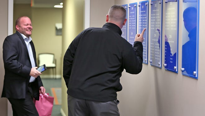 """Company founder, Mike Wood, left, laughs with Sr. Mortgage Consultant Grant Lyons as he poses by his name on the plaques posting the """"Wall of Champions"""" at Bailey & Wood Financial Group in Whiteland, Thursday, March 3, 2016."""