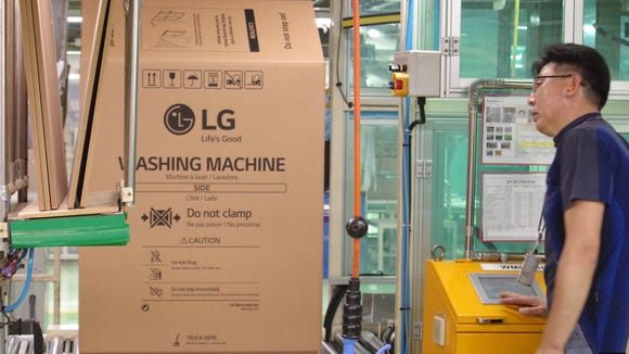 A worker inspects an LG washing machine at the company's factory in Changwon, South Korea