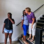 Becky Helne (far right), director of secondary education at Community Catholic Center, greets students Heaven Offutt (middle) and Angel Rocker as they enter the revamped Our Lady's School for the summer learning program in Portland, Tuesday June 23, 2015.