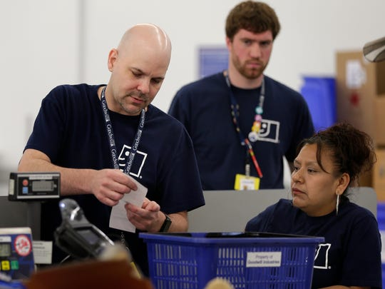 Goodwill leader Jebb Filz, left, looks over a receipt with Wanda Ruiz, right, and Grant Nelton in Appleton. After being released from prison seven years ago, Filz found help in a Goodwill program for former prisoners.