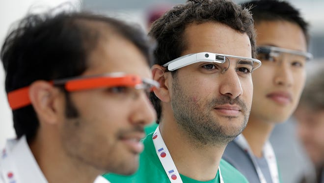 Google Glass team members wear Google Glass devices at a booth at Google I/O 2013 in San Francisco.