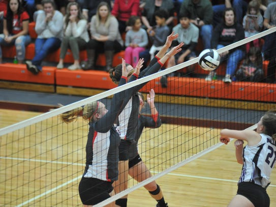 Lexi Evak and Courtney Pifher block an Ada spike at the net.