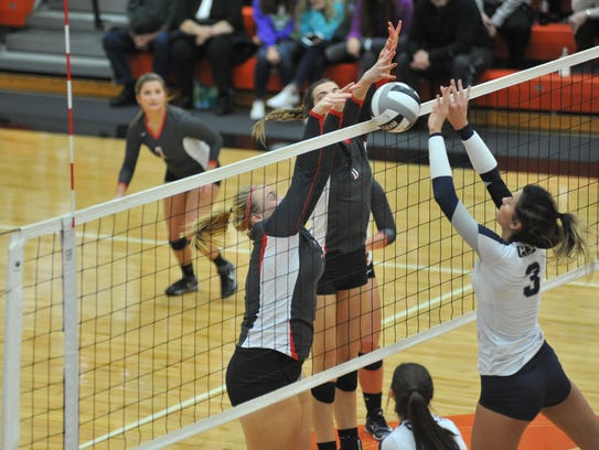 Courtney Pifher and Lexi Evak block Sydney Kin's tip