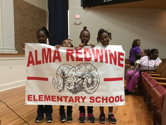 Alma Redwine students Faith Williams, Zoe Brunson, Tityana Jackson and Chloe Channy hold up a sign in support of their school at Tuesday's special board meeting.