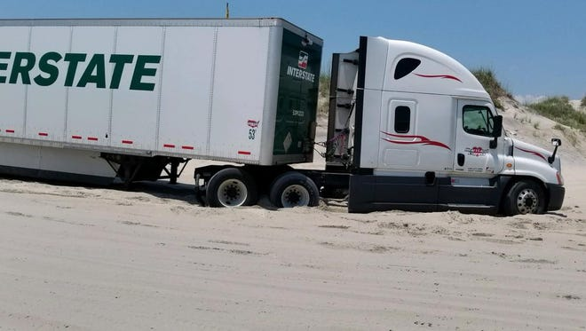 A tractor-trailer driver got stuck on the beach in the Outer Banks when he hit a dead end and tried to do a U-turn in the sand, according to media reports. Image courtesy of Wild OBX Facebook page.