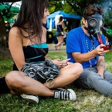 In this Sunday, Aug. 17, 2014 photo, a young couple trades off smoking out of a mask bong on the final day of Hempfest, Seattle's annual gathering to advocate the decriminalization of marijuana, at Myrtle Edwards Park on the Seattle waterfront. The three-day annual event includes political rallies, concerts, and an arts and crafts fair. (AP Photo/seattlepi.com, Jordan Stead) MAGS OUT; NO SALES; SEATTLE TIMES OUT; MANDATORY CREDIT; TV OUT