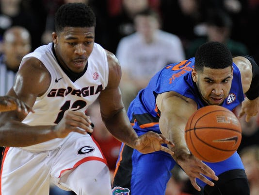 Georgia guard Kenny Gaines (12) and Florida guard Brandone Francis-Ramirez (2) compete for a loose ball during the first half of an NCAA college basketball game Tuesday, Feb. 16, 2016, in Athens, Ga. (AJ Reynolds/Athens Banner-Herald via AP)
