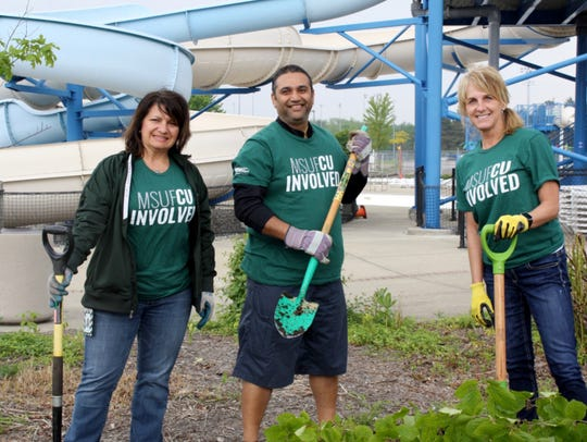 From left, MSU Federal Credit union employees Caroline VanHouten, Samip Patel and Michelle Baldino plant trees at the East Lansing Aquatic Center and Softball Complex in May.
