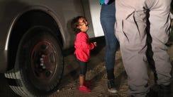 A two-year-old Honduran asylum seeker cries as her