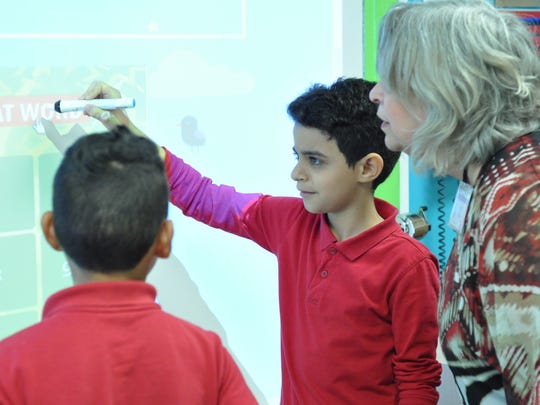 Martha Chapman, the Rapides Parish School District's English Language Acquisition facilitator, observes Cherokee Elementary students, including Bashar Shaibi from Yemen.