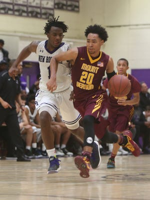 Mt. Vernon's Jason Douglas Stanley (20) drives to the basket in front of New Rochelle's Jaylin McGhee (1) during basketball action at New Rochelle High School Jan. 27, 2018. Mt. Vernon won the game 69-61.