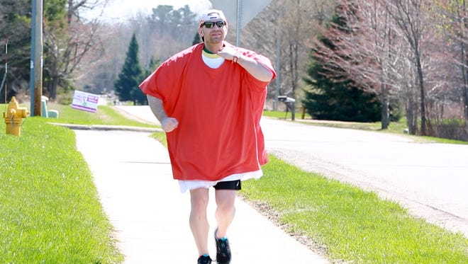 Steve Ruppel plods down the sidewalk near the Aspirus YMCA in Weston while burdened by 30-some T-shirts on Sunday, May 6, 2018. Ruppel set a unofficial Guinness World Record by completing the Journeys Half Marathon while wearing 60 shirts.