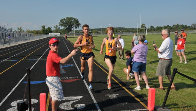 Port Huron Northern's Matt Thomas (left) and Bradley Mallory cross the finish line Tuesday at the Macomb Area Conference White Division jamboree. Mallory defeated Thomas by less than 1 second.