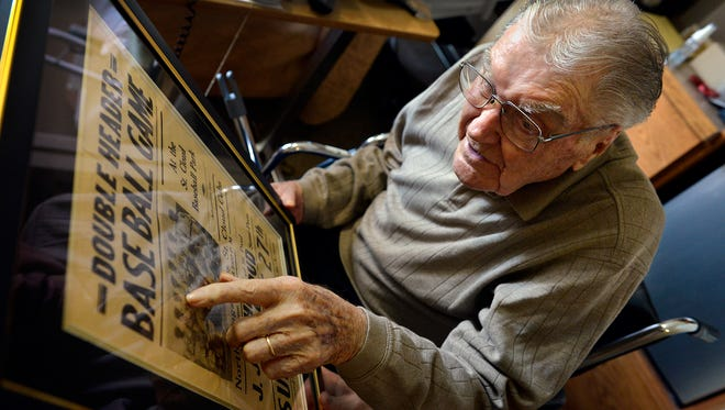 St. Benedict Senior Community resident Will Hirschfeld, 99, looks over a 1937 photo of his St. Cloud Semi-Pros baseball team from a poster advertising a doubleheader as he reminisces Thursday in his room. Hirschfeld turns 100 Aug. 9.