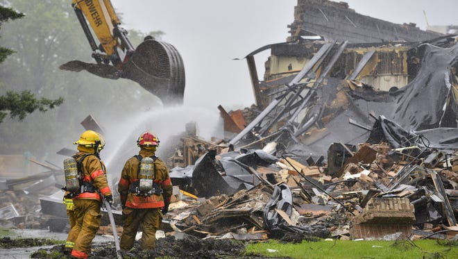 A backhoe works to take down walls as firefighters from St. Cloud and several other departments continue Sunday morning to fight an overnight fire that destroyed the Roosevelt Education Center.