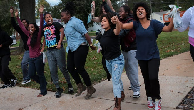 Ferguson, Mo., protesters leave arm-in-arm after being released from jail Friday. Protesters have been a constant presence in the St. Louis suburb in the nearly two months since Michael Brown was shot and killed by a police officer. A federal judge on Monday issued a preliminary injunction halting a police practice of requiring protesters to keep moving rather than stand.