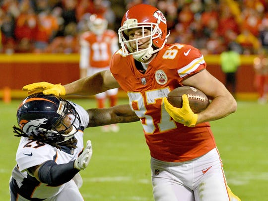 Chiefs tight end Travis Kelce (87) stiff-arms his way