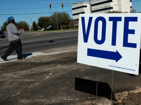 A pedestrian walks past a vote sign for the Senate District 26 runoff election outside the Rufus A Lewis Branch Library, which is a polling place, in Montgomery, Ala., on Tuesday, Feb. 27, 2018.