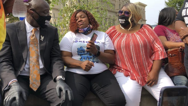 Tamika Palmer, Breonna Taylor's mother, in white beside Attorney Ben Crump, left, speak in Louisville, Ky., after settlement was announced. The city of Louisville will pay $12 million to the family of Breonna Taylor and reform police practices as part of a lawsuit settlement months after Taylor's slaying by police thrust the Black woman's name to the forefront of a national reckoning on race, Mayor Greg Fischer announced Tuesday.