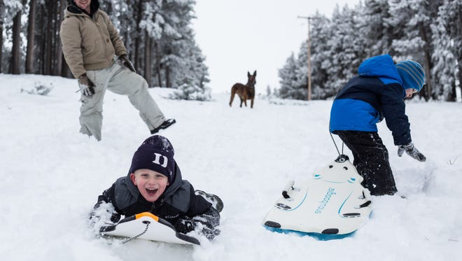 Kade Wheeler, 4, sleds on Casper Mountain with his father Seth, brother Krew, 5, and their Belgian Malinois, Patrick, on Tuesday, Dec. 16, 2014, south of Casper, Wyo. Casper Mountain received close to a foot of snow in the recent storm. (AP Photo/Casper Star-Tribune, Ryan Dorgan)
