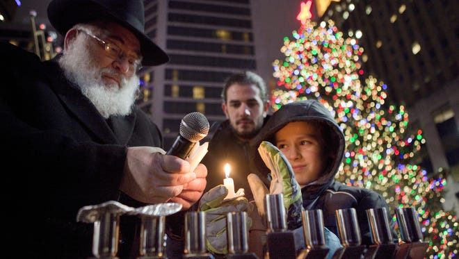Rabbi Sholom B. Kalmanson, executive Vice President of Chabad of Southern Ohio, helps Yossi Creeger, 10 of Clifton, light a menorah on Fountain Square on Wednesday, December 17, 2014.