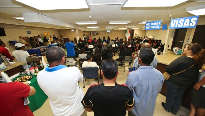 FILE - In this April 23, 2014, file photo, a crowd of approximately 80 immigrants fill a room as they listen to officials explain the process of getting a drivers license, during an information session at the Mexican Consulate, in San Diego. California is gearing up to start issuing driver's licenses to immigrants in the country illegally in a bid to make the roads safer that could also give more than a million people access to state-issued identification. (AP Photo/Lenny Ignelzi,File)