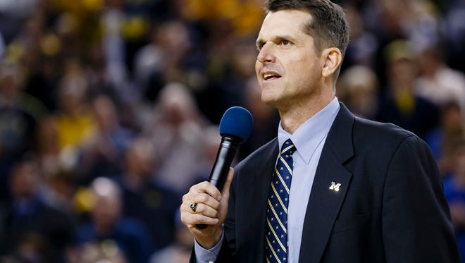 Michigan Wolverines head football coach Jim Harbaugh address the crowd during halftime of the game against the Illinois Fighting Illini at Crisler Center.