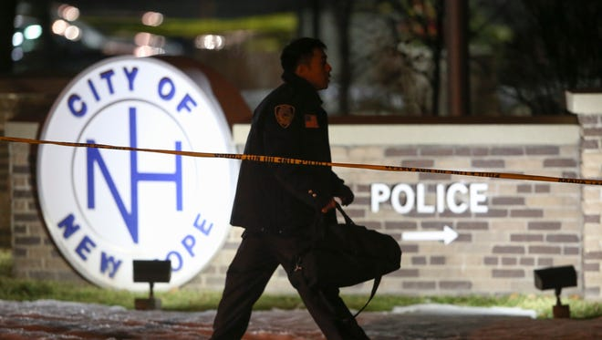 An emergency personnel member walks outside the New Hope Police Department after two police officers were shot Monday, Jan. 26, 2015 in New Hope, Minn.
