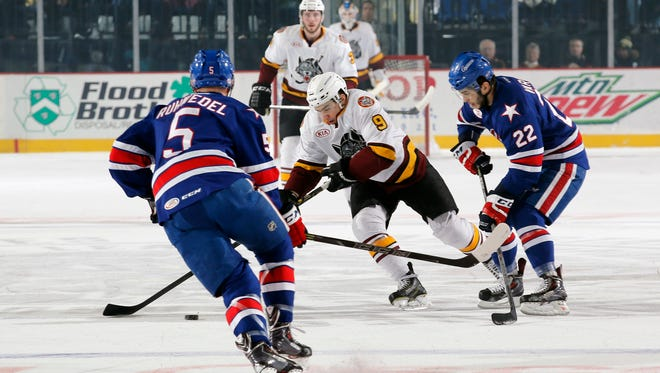 Amerks center Phil Varone and defenseman Chad Ruhwedel converge on puck-carrying Wolves right winger Shane Harper.